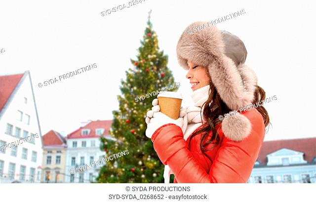 woman with coffee over christmas tree in tallinn