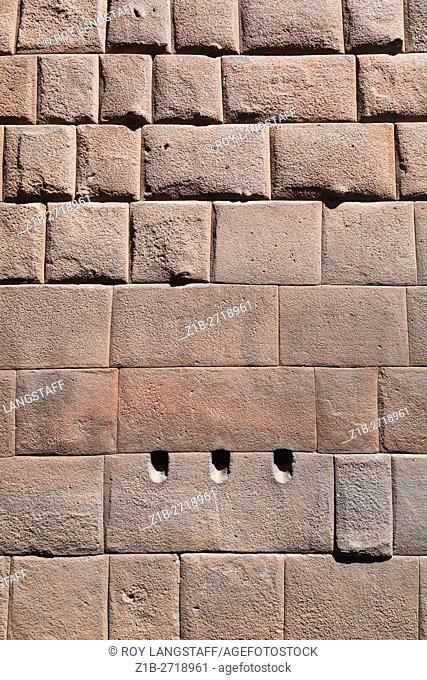 Outside wall of the Koricancha Incan temple with three holes to drain blood from the interior sacrificial altar