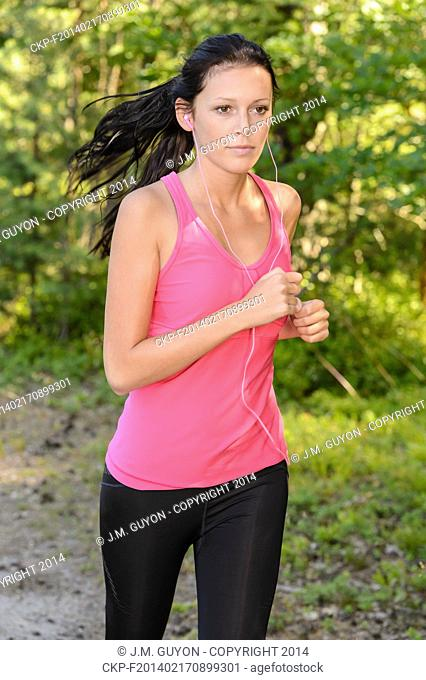 Running woman outdoor with headphones close-up