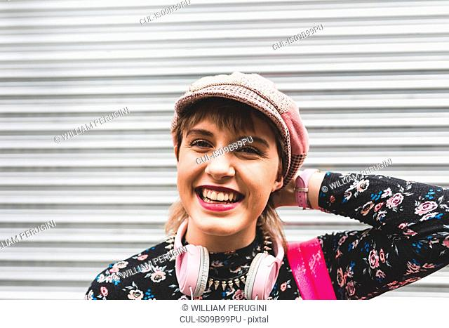 Portrait of stylish young woman in city in baker boy hat