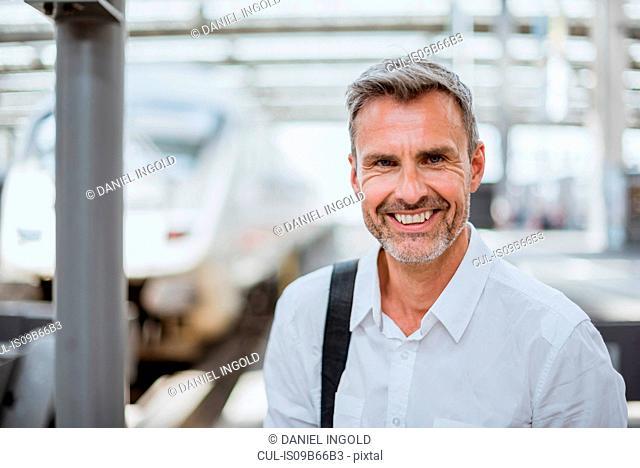 Portrait of mature man on station platform, smiling