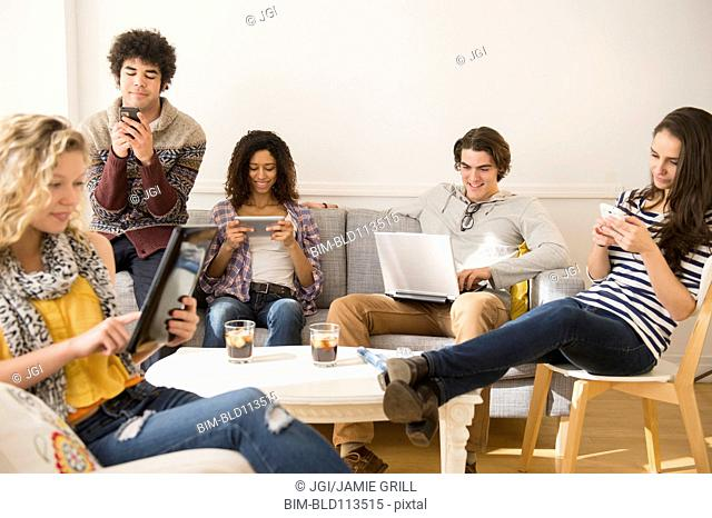 Friends using technology in living room