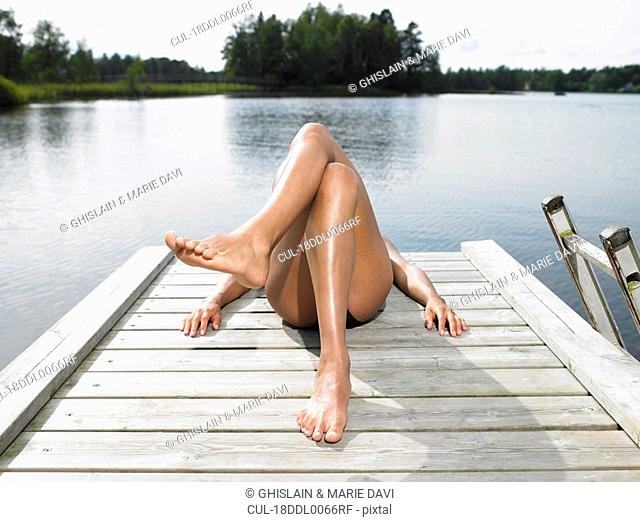 Woman tanning on a dock