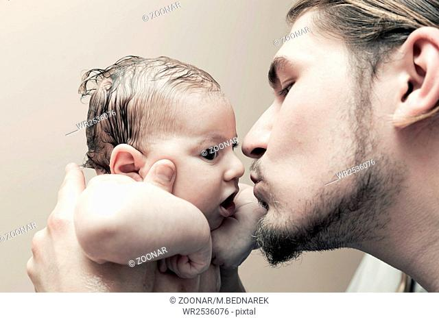 Father with his young baby cuddling and kissing him on cheek. Parenthood