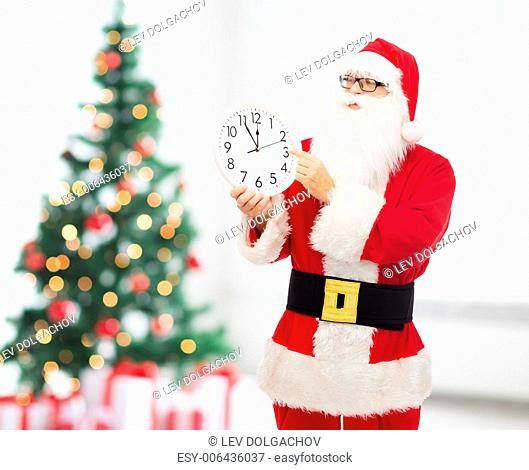 christmas, holidays and people concept - man in costume of santa claus with clock showing twelve pointing finger over living room and tree background