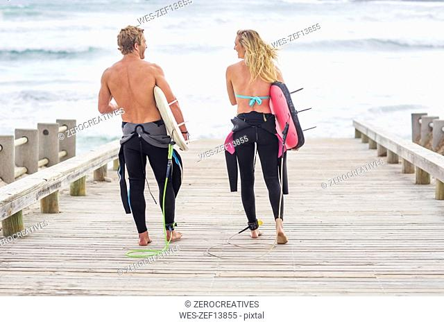 Couple walking to beach with surfboards