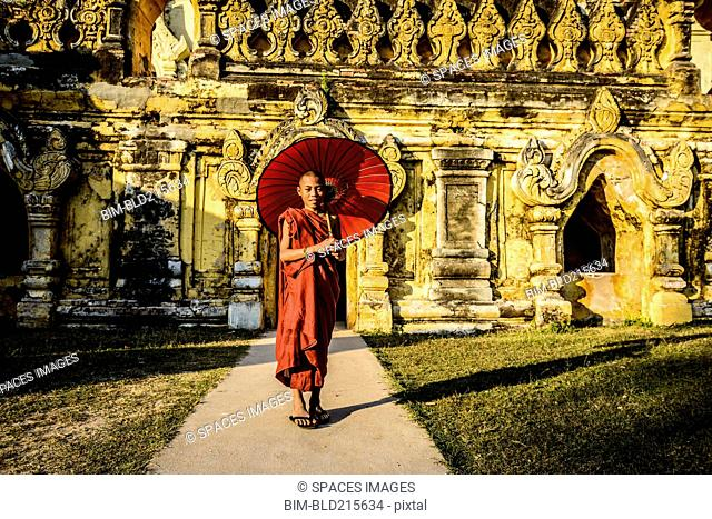 Asian monk-in-training holding parasol outside ornate temple