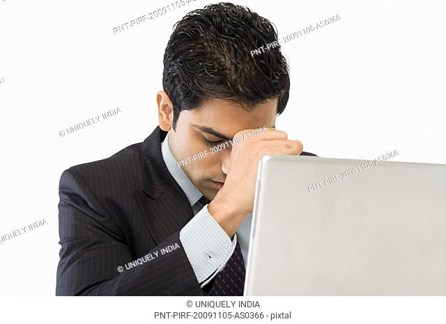 Businessman looking worried in front of a laptop