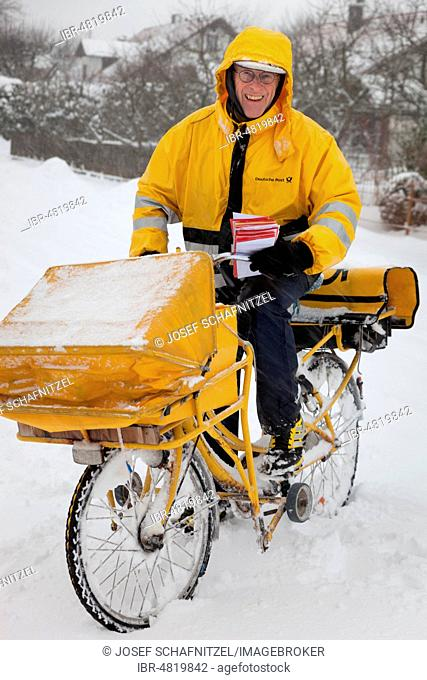 Man, postman, postman on yellow post bicycle in winter conditions, Bavaria, Germany