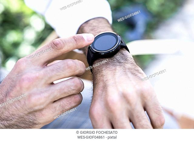 Close-up of man using smartwatch outdoors