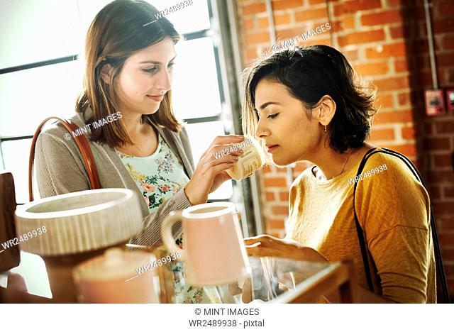 Two young women in a shop, smelling a jar of lavender salve