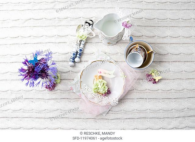 A retro place setting decorated with flowers on a knitted tablecloth