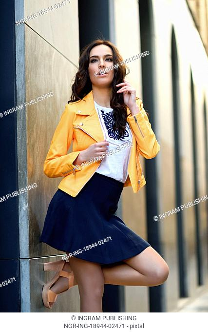 Young brunette woman, model of fashion, wearing orange modern jacket and blue skirt in urban background