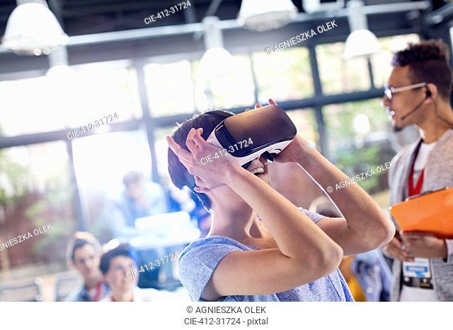 Woman trying virtual reality stimulator glasses at technology conference