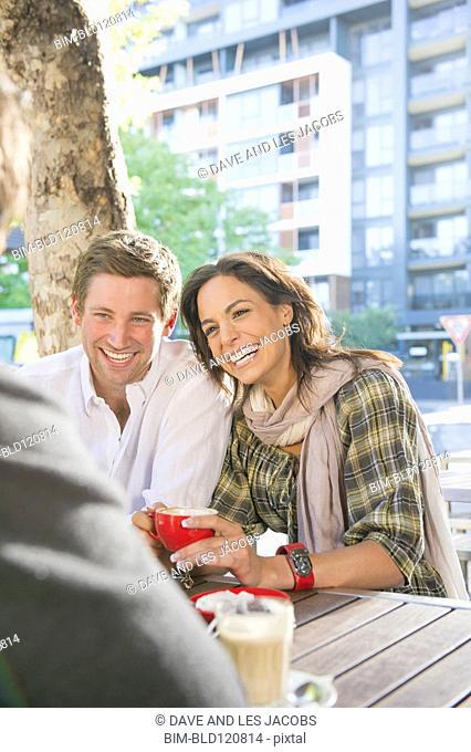 Friends having coffee at sidewalk cafe