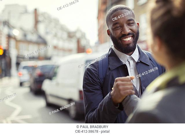 Smiling businessman shaking hands with colleague on urban street