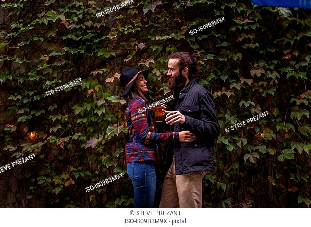 Young couple laughing in beer garden in evening, Brooklyn, New York, USA