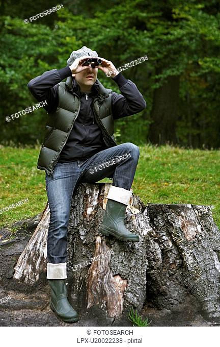 Man Using Binoculars on Tree Stump