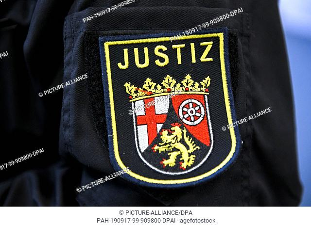 16 September 2019, Rhineland-Palatinate, Mainz: The coat of arms of the Justice Department of Rhineland-Palatinate can be seen on the overall of a prison...