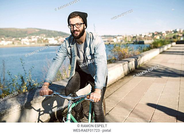 Smiling young man riding his fixie bike at the waterfront