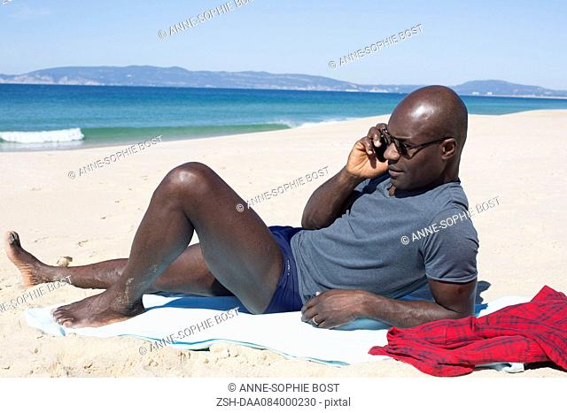 Man lying on beach, talking on cell phone