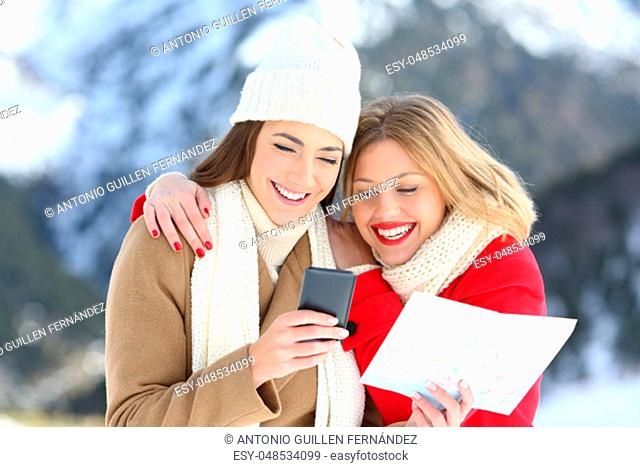 Two happy tourists searching location on line in a smart phone in winter holidays in a snowy mountain