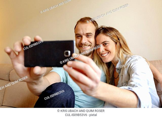 Mid adult couple relaxing on sofa, taking selfie, using smartphone