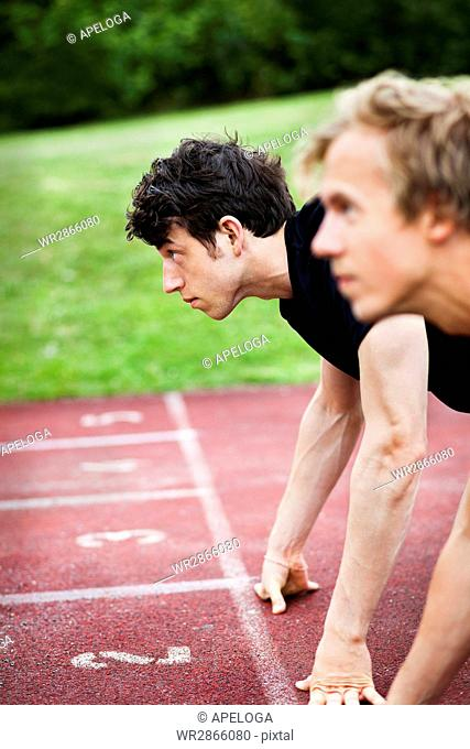Side view of young athletes leaning on starting line at tracks