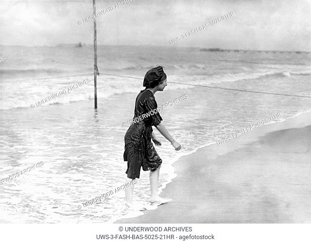 France: c. 1905.A woman exits from the ocean in a bedraggled looking bathing suit