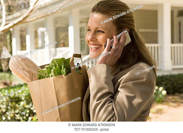 Woman carrying groceries and talking on telephone
