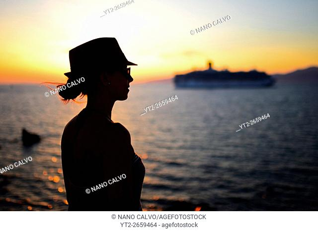 Young woman enjoying views of Mykonos town at sunset, Greece