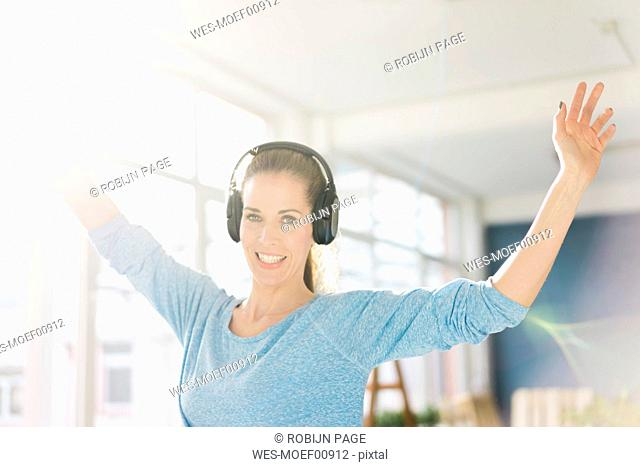 Portrait of a beautiful woman, listening music with headphones