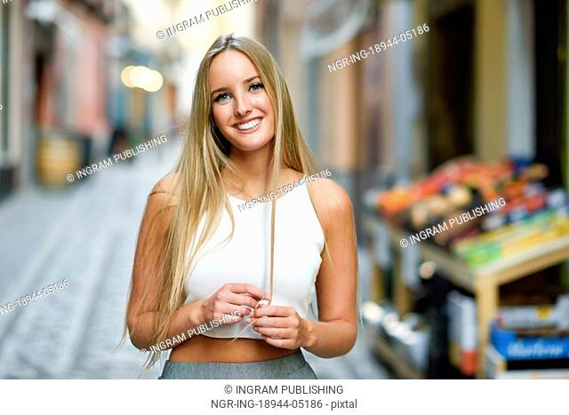 Smiling young woman in urban background. Blond girl wearing with nice hair casual clothes in the street. Straight hairstyle
