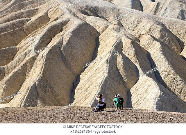 A pair of photographers are perched on the hillside at Zabriskie Point in Death Valley to catch golden hour light creating deep shadows in the sandstone rock...