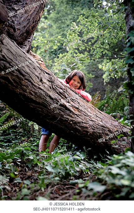 Portrait of smiling girl (6-7) leaning against tree trunk in forest