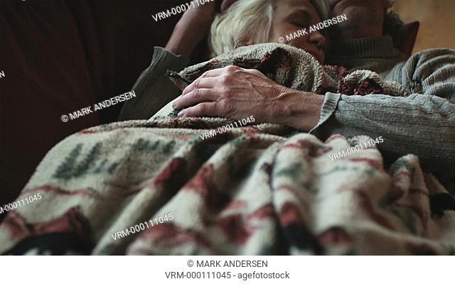mature couple taking a nap on the couch together