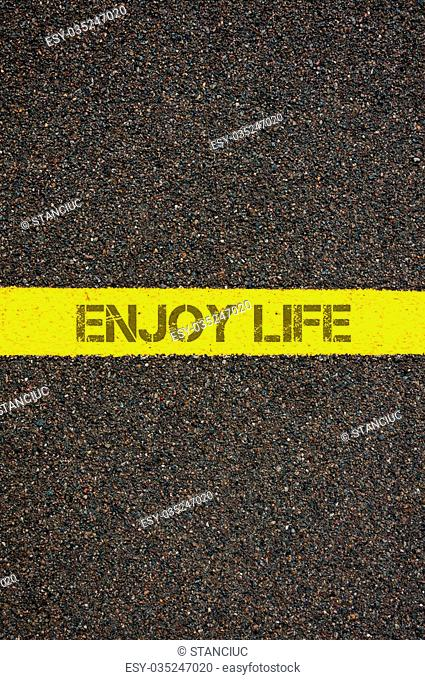 Road marking yellow paint dividing line with words ENJOY LIFE, concept image
