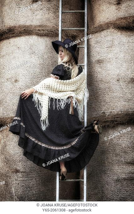 a beautiful girl on a ladder in a haystack