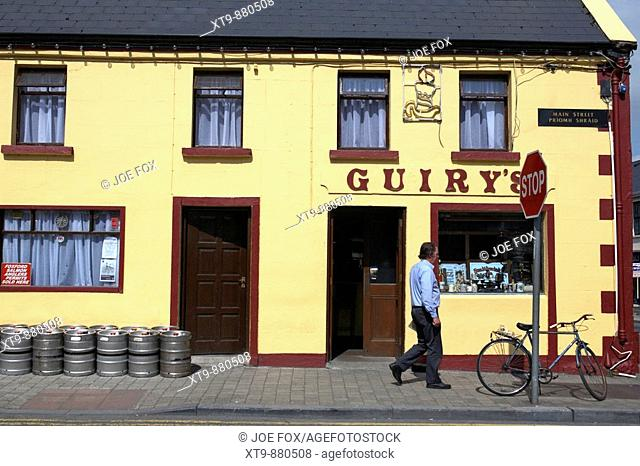 man walking past guirys irish pub in foxford a traditional small irish town in county mayo republic of ireland