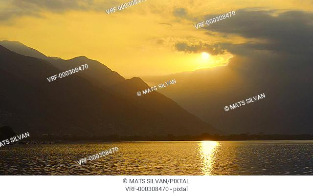 Sunset over Alpine Lake Maggiore with Clouds and Mountain in Locarno, Switzerland