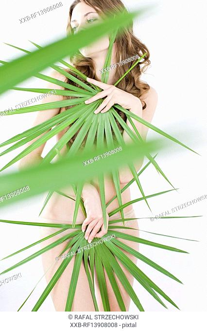 young woman covering nude body with plant