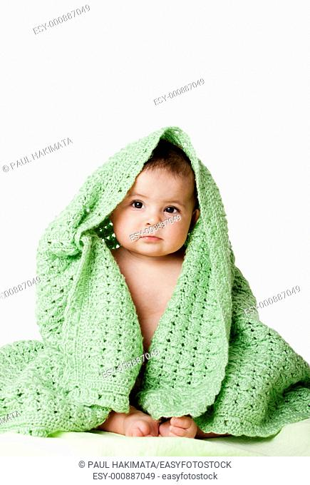Beautiful cute innocent Caucasian Hispanic baby face while sitting and covered between green knitted blankets, isolated