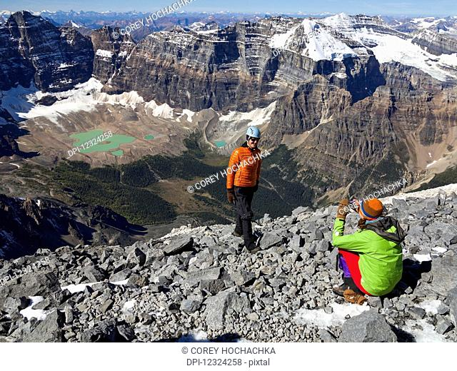 A father posing while his daughter takes a picture during a hike in the Rocky Mountains; Banff, Alberta, Canada