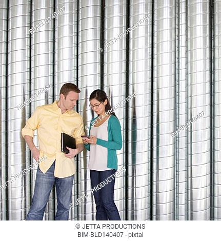 Business people using cell phone near metal wall