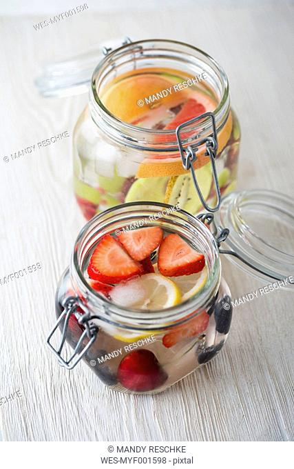 Two jars of cooled water flavoured with different fruits