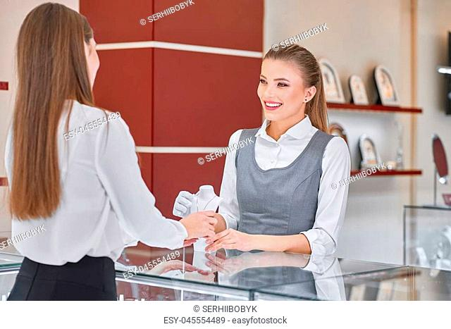 Pretty young female jewelry worker in white blouse and grey uniform is helping to choose a necklace for a female visitor wearing smart clothes such as black...