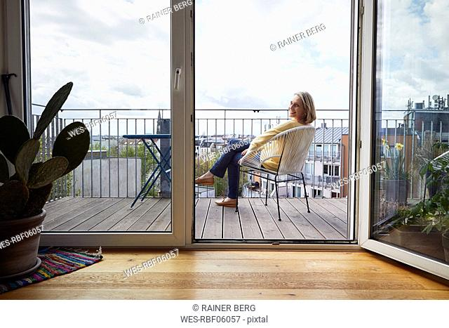 Smiling mature woman at home sitting on balcony