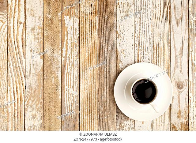 espresso coffee in a white china cup over grange wood surface with paint peeling off