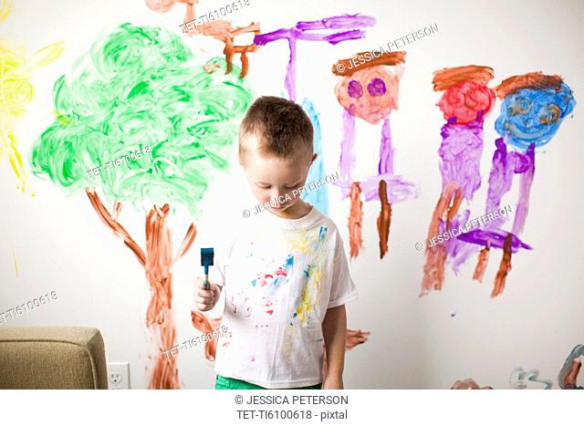 Toddler boy 2-3 standing in front of painted wall with guilt expression on his face