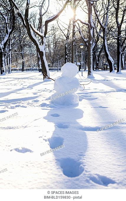 Snowman and footprints in snowy park
